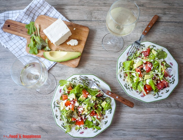 Rich, green summer salad with avocado, tomatoes, Feta cheese and fresh salad leaves.